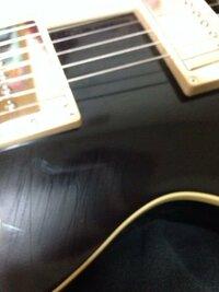 昨日買ったばかりのギターにこんな傷がついてしまいました。。。弾き方が悪いと思うんですけど… 塗装はラッカーフィニッシュなんですけど、消す方法とかありませんかね…?
