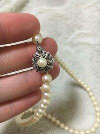 真珠の見分け方について はじめまして。 祖母から40年前に購入したという真珠のネックレスをいただきました。 いままで数回使用したのですが、そのネックレスのケースの中に15000円で購入したという領収書を発見し、本物かどうか疑っています。  もしフェイクなら、本物を購入したいです。 どうかお詳しい方教えてください。  自分なりに調べたのですが、手にした感じは重みがあるように思います。 留め具は...