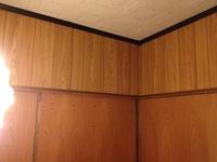 プリント化粧合板の壁紙貼りについて  以前も質問させていただいた者です。  写真のような木目の壁をリフォームしたいのですが、色々悩んだ挙句、のり付きの壁紙を貼ることにしました。 http://www.diy-shop.jp/item.php?cc=0000014303  しかし、ご覧のように、木と木のつなぎ合わせ部分?に3mmほどの隙間が縦に入っており、この隙間を埋めなければなら...