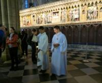 この少年と手に持っているものはなんですか? パリのノートルダム大聖堂で写真の少年たちを見かけました。 彼らの役割と手に持っている物について教えて下さい。  後日ルーブル美術館にてナポレオンの戴冠式の絵...