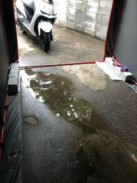 駐車場の水溜りについて 雨が降ると写真の様に駐車場に水溜りが出来てしまいます。解消するにはどのような手段がありますでしょうか。なるべく費用がかからない方法だと助かります。  バイク用の簡易ガレージの中...