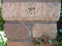 屋外のレンガ(コンクリート? )に金属のプレートを貼るための適した接着剤が知りたい。  写真にあるようなレンガ風の壁面に金属プレートを接着させたいです。  ・壁面は、添付写真にあるとおり、表面がとこ...