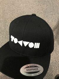 コイン100枚 こちらの帽子は、シン・エヴァの公開決定を祝してオープンした池袋のエヴァンゲリヲンストアで買ったものなのですが、この文字?列は一体なにを表していて、どういった意味なのでしょうか...。