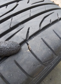 タイヤパンク修理跡の亀裂、修理しなくてよいかするべきものか  タイヤ接地面、パンク修理跡の亀裂はそのまま使ってもいいものか、店で補修すべきものかを伺いたいです。 サマータイヤを外したら、タイヤ接地面に横方向の亀裂が入っているのが見えました。 亀裂が入っている部分は春先に釘を踏んでしまい、外面修理で直したところです。 正直業者任せにして修理後のチェックをしなかったので、修理時にすでにこ...