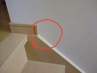 階段室の幕板の施工方式について教えてください。階段の窓枠(下)と、幕板が干渉します。 当初は、幕板なしでの施工でしたが、クロスにひび割れが発生したために、幕板を取り付けます。 干渉 するのは約5mm幕板の上側を切り欠きしないといけません。 階段上の幅木と幕板の上面を合わせた場合です。 どのように幕板を取り付けするのがよいでしょうか?