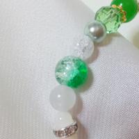 パワーストーンに詳しい方よろしくお願いします。 写真では分かりにくいとは思うのですが、写真の真ん中の3つはパワーストーンでしょうか、ビーズでしょうか。 パワーストーンだった場合、名前は何ですか? 教えて頂きたいです。  真ん中の緑の物は、半分が透明、半分が緑です。 その上の物はクラック水晶かなと思っています。 下の物は乳白色でもやもやしています。