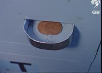 この硬貨は何と言う硬貨でしょうか? 今日は、動画を見ていたらどうしても気になったので 質問しました。 名前と、現在の日本円にしてどれぐらいの価値があるか教えて頂きたいです、ちなみに この動画は1964年 ロンドンでの自動販売機についての動画でした、 調べても中々出てこなく、恥ずかしながら英語の ページばかりで自分では把握できませんでした。 詳しい方、どうか回答お願い致します。