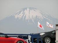 東名高速道路の足柄サービエリアで富士山を取った写真です。後で見てみると下の方に2台の車が映っています。左の赤いスポーツカーっぽい車の車名を教えて頂きたいです。よろしくお願いします。