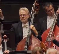 真ん中の白い髭のおじさんがコントラバスのE.A線のペグの所に付けている銀色のパーツは一体なんなのでしょうか? ラフマニノフ交響曲第二番で、楽章の合間にE線をDにチューニングせよ、という指示があるのですが...