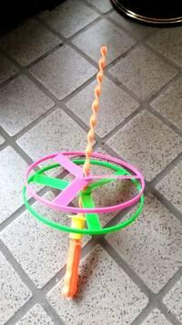 大掃除していて出てきたのですが、これ何という名前のおもちゃか分かりますか? 黄色のつまみを思いっきり押しだして丸いやつが飛ぶおもちゃなんですが……