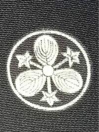 家紋について質問です。 この画像の家紋の名前がわかる方いらっしゃいますか? 画像は母の留袖を撮影したものです。 鯉のぼりと共に立てる幟旗に家紋を入れるために調査しております。宜しくお願いします。