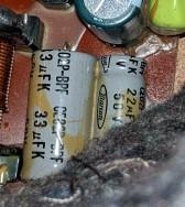 写真は1985年発売のオンキョースピーカーのネットワークの一部です。グレーの部品も電解コンデンサーでしょうか?