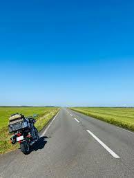 晴れた日の昼間の空に関する質問です。下の画像の上の方の青空の色の濃さと道路の上の青空の色の濃さが違うのはなぜでしょうか?