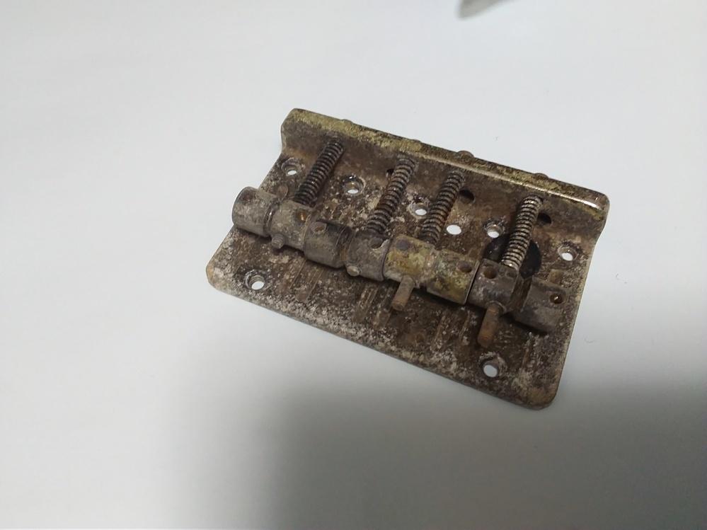 金属部品の錆びとり方法でお知恵を貸してください 楽器(エレキベース)のブッリッジを長期保管していたら 写真のように茶色~灰色系の錆びが浮いた状態になっています 例えば酢に入れるとか、錆びとり剤を使うなど XXX液につけて還元させる方法はありませんか? 金ブラシで擦るのはなるべく避けたい 材質は磁石がくっつくので鉄系素材 メッキ処理がされているかは不明
