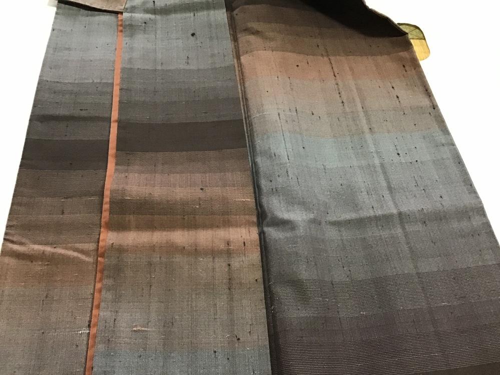 着物の生地のアップになります。真綿系程のフカフカ感はありませんが、縦にポコポコと黒い節? が、縦糸に使われている様です。横には 糸を繋いだ時のものが あります。 これだけの情報で、産地とか 紬の名称が わかりますでしょうか? 宜しくお願いします。