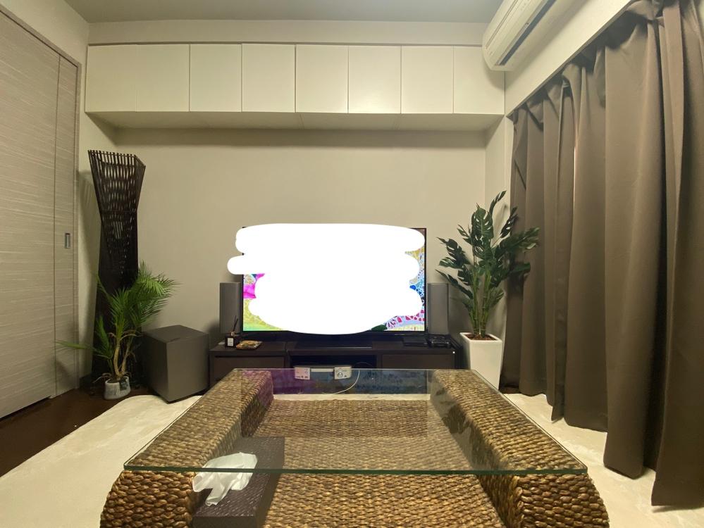 インテリア:テレビ横の人口観葉植物の配置について、アドバイスをお願いします。 添付写真は、我が家のリビングです。 贈り物でいただいたフェイクグリーンをテレビ脇に置きたいのですが、どう配置すればバランスが良くなるでしょうか? 現在の配置は左から順に、 バリ風のスタンドライト → 70cmの椰子 → スピーカー → テレビ台 → 120cmのモンステラ です。 今のままだと、アンバランスな気もします。 フェイクグリーンは新たに追加購入も可能です。 よろしければ、アドバイスいただけると嬉しいです。