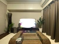 インテリア:テレビ横の人口観葉植物の配置について、アドバイスをお願いします。  添付写真は、我が家のリビングです。 贈り物でいただいたフェイクグリーンをテレビ脇に置きたいのですが、どう配置すればバランスが良くなるでしょうか?  現在の配置は左から順に、 バリ風のスタンドライト → 70cmの椰子 → スピーカー → テレビ台 → 120cmのモンステラ  です。  今のままだ...