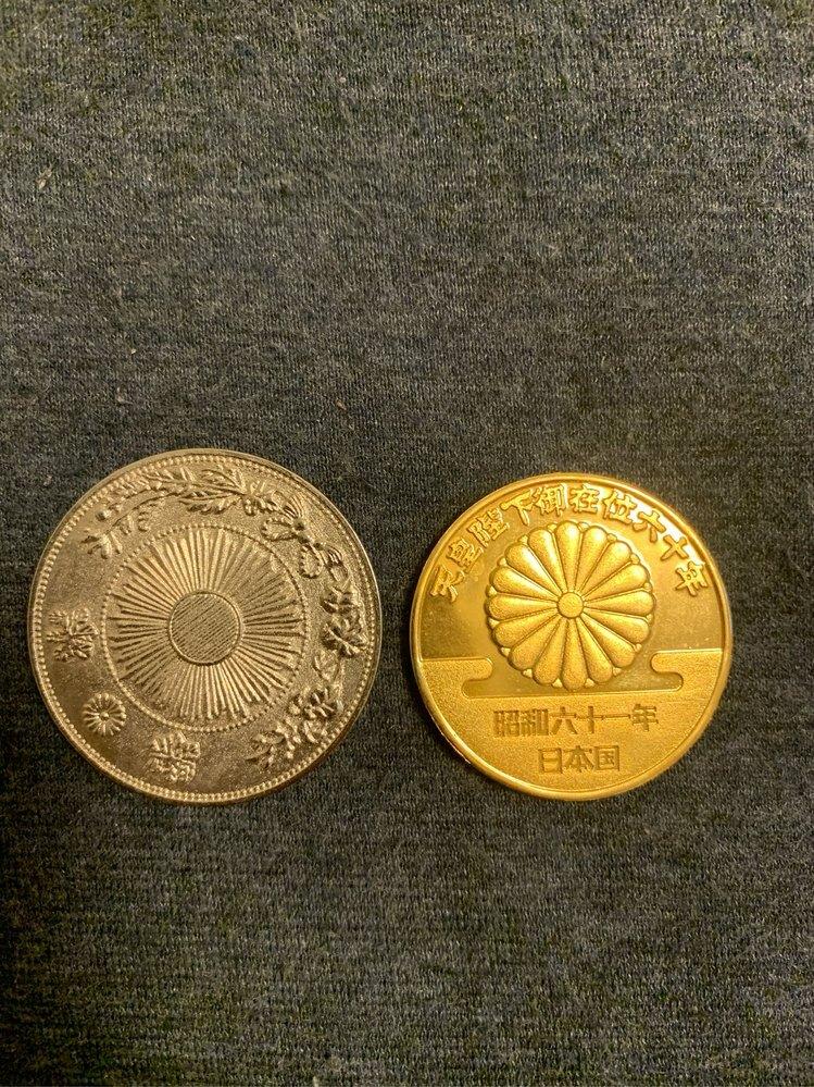 部屋を掃除していたら不思議なものを見つけました。これは一体なんなのでしょうか? 金色の硬貨の方には天皇陛下御在位六十年 昭和六十一年 日本国と書かれており、裏には天皇萬歳と書かれています。銀色の硬貨の方には大日本明治三年一圓と書かれています。わかる方ぜひ教えてくだはい!