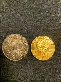 部屋を掃除していたら不思議なものを見つけました。これは一体なんなのでしょうか? 金色の硬貨の方には天皇陛下御在位六十年 昭和六十一年 日本国と書かれており、裏には天皇萬歳と書かれています。銀色の硬貨の...