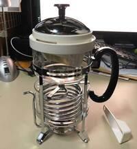 謎の器具(ポット?)の使い方が分かりません。そもそも、コーヒーかお茶かも定かではありません。 漏斗の形状からコーヒーではないかと思っています。 上と下に二つの容器があり、上の容器には漏斗が付いています。その容器の底からパイプがつながり、下の容器の中でスプリング状に巻かれています。液体がこの中を通って冷却されるものと思われます。 アイスコーヒーメーカーかと思いましたが、パイプの先は低い部分で注...