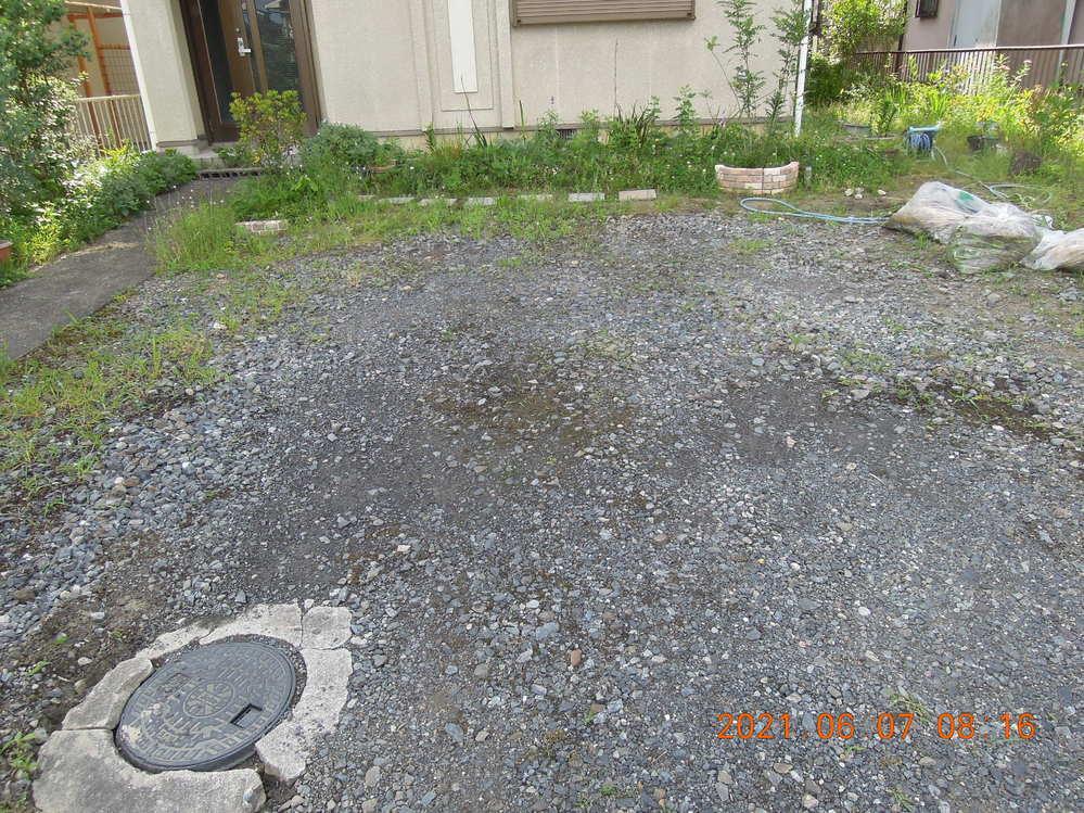 駐車場のことで教えて下さい。 駐車場を簡単に見栄えよく安価で仕上げる方法を教えて下さい。今現在の駐車場は写真のように薄く砕石を置いただけのものなのででこぼこがあり雑草が出てきます。時々除草剤の液を振りかけて退治しているのですが、同じことの繰り返しです。良い方法があれば教えて下さい。間口7m奥行5,5mで車2・3台が置けます。 ①砕石の量をもっと増やせば雑草は出なくなるでしょうか。 ②現在砕石の下に防草シートは敷いていません。今から防草シートを敷くのは大変ですし防草シートにも劣化・寿命があると思うのですが。 ③奥に30cm四方のコンクリートの板がありますが近所にこれを敷き詰めて駐車場にしている家がありました。この場合強度は大丈夫でしょうか。 ④①と③の折衷で所々にコンクリートの板を置きその間に砕石を敷き詰めるとデザイン性も出てくると思うのですが。 ⑤一面コンクリートにする。これは自分ですることが出来ますか。業者に頼んだ場合この広さではいくらくらいかかりますか。近所のこの方法のところの多くが経年劣化で黒ずんでいて見栄えが悪く、撤去の時も大変だと思うのですが。 何か良い方法があれば教えて下さい。