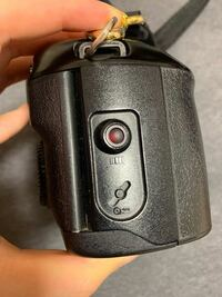 Canon EOS 100qd フィルムカメラです。 この巻き戻しボタンの上にある赤っぽいボタン、何に使うものか教えてください。