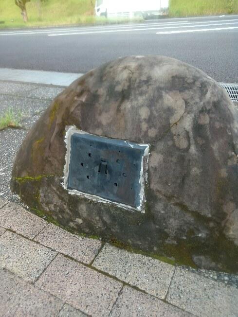 宮崎自動車道路のパーキング内で、車止め?に使われている石のひとつの画像です。 幾つか石は並んでいるのですが、ひとつだけにこれがあります。 これは一体何なのか、気になっています。 宜しくお願い致します。