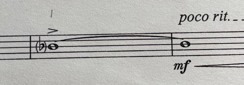 吹奏楽の楽譜で画像にある(♭)というのがでてきたのですがどういう意味でしょうか?この場合フラットはつけるのですか?つかないのですか?