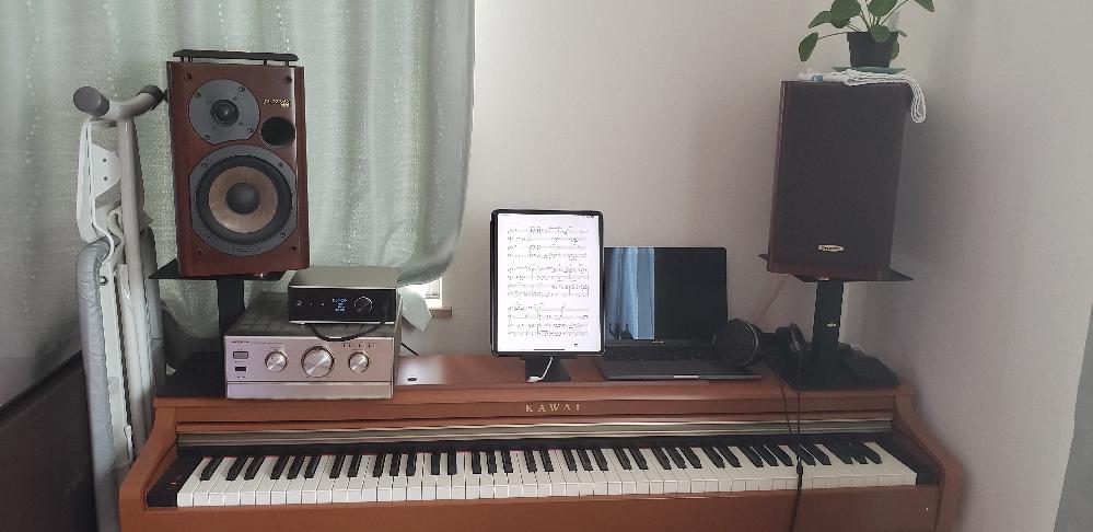 電子ピアノ用モニタースピーカー選び 電子ピアノの練習で気持ちよく弾けるスピーカー(と場合によってはUSB DAC付プリメイン)を探しています。 ピアノは幼少期に数年やり、40代でコロナ禍で始めた趣味です。DTM も少しかじっています。 電子ピアノ(Kawai) as鍵盤 + MacBookPro + 音源 VSL Synchron Yamaha CFX までは固定で考えており、その先ヘッドホンでの環境は気に入っているのですが、 手持ちの環境だと、スピーカーに出した途端ペコペコな音になり、弾く気が削がれてしまいます。 嫁と娘もピアノを弾きますので、近所に響くような大きな音を出したいわけでなく、近くで聞こえて、特に奏者中心に気持ちよく弾けるよう/聴かせられるような環境ができないかと模索しています。 いままで試した環境です。 環境① ヘッドホン(とても気に入っている) MacBookPro -> ヘッドホンアンプ DENON DA-310USB -> ヘッドホン SENNHEISER HD650 環境②(DTM環境から融通,試しのみ) MacBookPro -> USB IF RME Fireface UC -> Yamaha HS5 環境③ MacBookPro -> DENON DA-310USB -> ONKYO Intec275 A-922M ltd -> D-202AX ltd ②はサラウンドの様にもやつき、ダイレクト感がなく、一聴して違うと感じてしまいました。 ③は20年ほど前のコンポの流用です。 DA-310USBの HPジャックと背面LineOutの2種類で繋げました。 音のバランスもヘッドホンからは見劣りしますし、なによりアタック感がだせず。 弾いてもペコペコしてテンションが上がりません ①+③の現状の写真を添付します。 この様な環境で弾いて楽しむのに、スピーカー系のオーディオ機器選びをどういった方向で探し始めたらよいでしょうか? ・環境的にあまり大きい機材は設置が難しいと考えています。 ・テンション上げて気持ちよく弾きたいので、原音忠実なモニター系より リスニング系? ・パッシブ/アクティブ? ・ニアフィールド?小型?低音足りるのかな? ・予算は決めていないのですが、試聴で納得いけば20程度は想定 ウェブやYouTube でも、ピアノ音源どんどん良くなっているからと、PC+高品位音源環境を進めるような記事はちょこちょこ見るのですが、ではモニタースピーカーって具体的にどんな?まで語ってくれているものがあまりなく、ここで質問してみようと考えた次第です。よろしくお願いいたします。