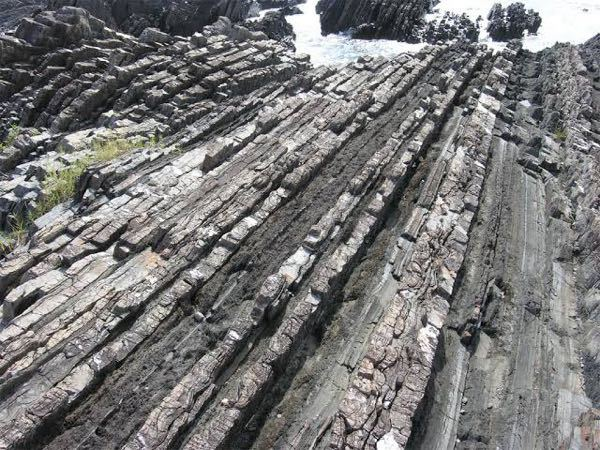 地学基礎です。 砂泥互層は砂岩と泥岩が交互に堆積したものですよね。なんでこの写真はそれが横向きになっているんですか。