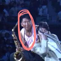尾崎豊のライブについてです。 1987年に有明コロシアムで『Bow!』という曲が歌われたんですが、その時のサックス奏者を教えてください。 写真のオレンジ色の○でかこってある人です。