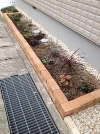 側溝沿いにレンガ/ブロックで花壇を造りたい 画像のように、側溝沿いをレンガ/ブロックで囲い、花壇を造りたいです。 画像は横積みですが、縦積みにしたいです。 自分でやります。 花壇は道路面より高くします。  花壇の層は、 土→4号砕石30cm→透水シート→黒土20cm となっています。  この場合、レンガ/ブロックは、側溝にモルタルを塗って接着しても大丈夫でしょうか。 4号砕石の部分がガタガタです。
