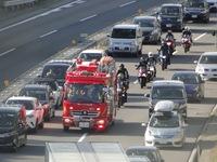 高速道路上で緊急走行中の緊急車両をバイクで追尾し、路肩に寄せて止まっている車両を抜くのは法律的に大丈夫なのでしょうか?画像のような状況です。