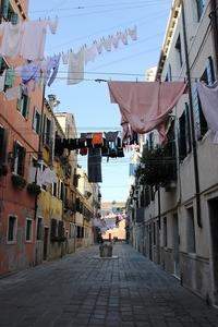 建物をつなぐ紐に、洗濯物を干すって効率よいのですか? 海外の写真をみると、この画像のように建物をつなぐ紐があって、そこに洗濯物が干されていることがあります。  これって左右の住人共有の紐なのでしょうか...