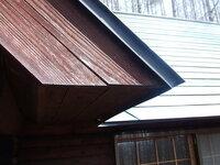 トイの新設に使う 雨どい金具 写真のような場所にトイを新設します。 105mmのトイを付けたいのですが、金属金具の取り付けが屋根の「軒の天井部」になるのですが(どこでもあるような屋根だと思うのですが???) 金具をみてもこのようなところに付ける感じの金具が見当たりません。  どういう金具になるのでしょうか?