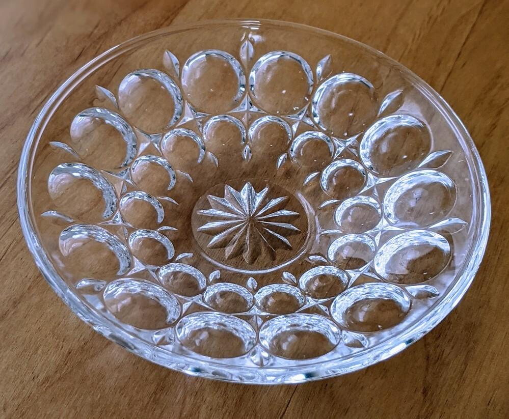 このお皿に見覚えのある方、教えて下さい! 妻のお気に入りの小皿を私の不注意でキッチンで落として割ってしまいました。直径10cm程でガラス製でディンプル(丸い凹み)が沢山あります。とても小さく、醤油皿として使っていました。 どこでいつ購入したのか、全く覚えていないらしく、、メーカーや売っている場所がわかる方がいましたら教えて頂けますと大変助かります!