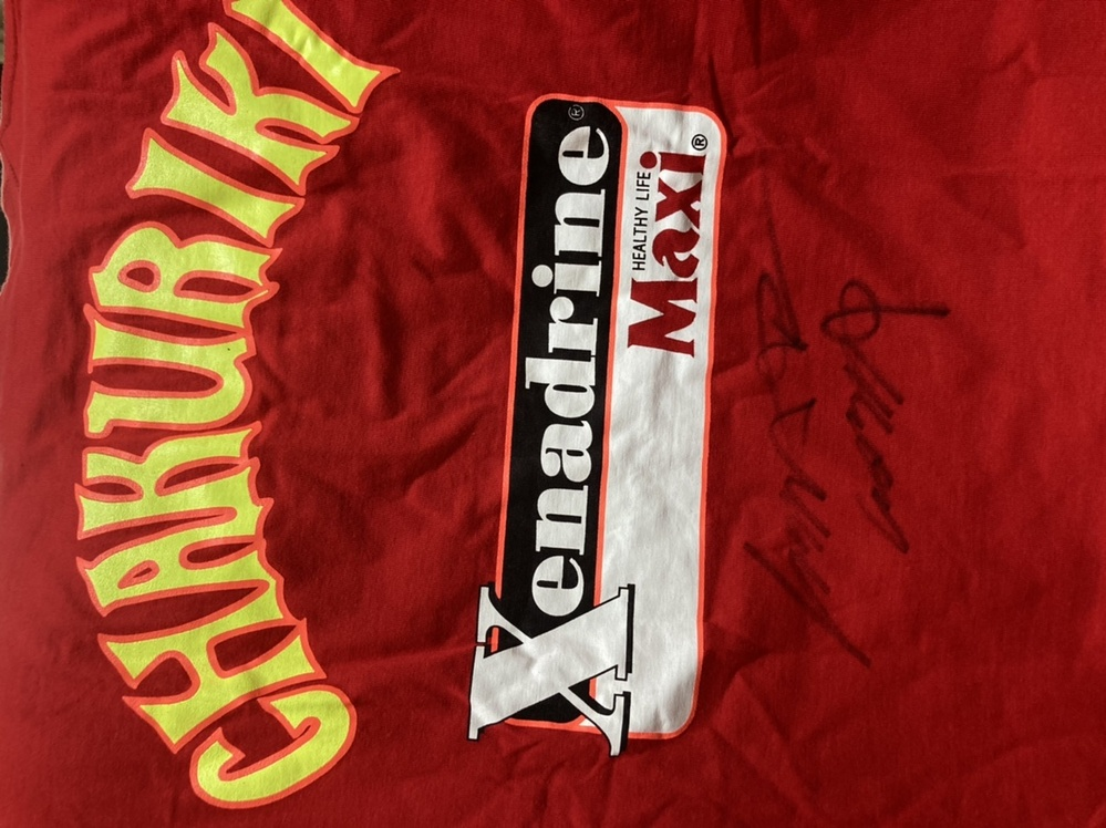 ドージョーチャクリキのTシャツになりますが、こちらのサインが誰のサインかわかりますか?