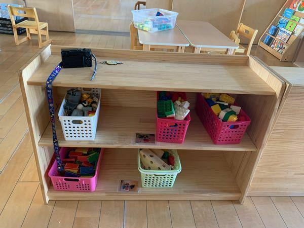 2歳児担任です。 初めての乳児で困っていることがあります。 写真のような棚があり、その上で玩具を広げるこが沢山います。近くに机もあり座ってねと声をかけて居ますが遊んでいます。そこで棚の上になにか楽しいものを置こうかと悩んでいます。それかイラストを貼るなど。。 何か良いアイデアがあれば教えてください!