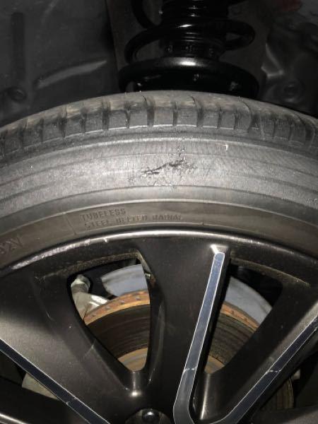 車・タイヤに詳しい方に質問です 写真付きで再投稿します。 中古車を購入してただいま納車待ちです。 担当の方から電話がありました。 要約すると「恐らく縁石に乗り上げたのか、左前のタイヤに小さなえぐれがある。車検がどうこうという程ではない。何か大きな問題がある訳ではないがお知らせしておく」とのことでした。 この場合、みなさんだったらどう対応しますか? そのままにするか1本だけ替えるか、悩んでいます……。 タイヤは5分ほど残っているそうです。 万が一バーストしたら…と考えると替えた方が良いのかな?と思いますが、いまいち分かりません…。