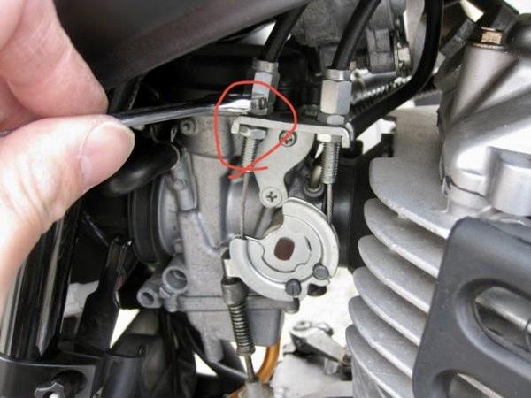 SR400のスロットルケーブルについて質問があります。 赤丸のところの下側のナットはどうやって締めれば良いのでしょうか? スパナを入れてもステーの爪が邪魔でほとんど可動域がありません。