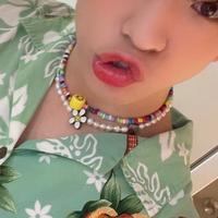 この画像に写っている花にニコちゃんマークの付いた、パールのネックレスを探しています。ブランド名や販売元など、どなたかわかる方いませんか?