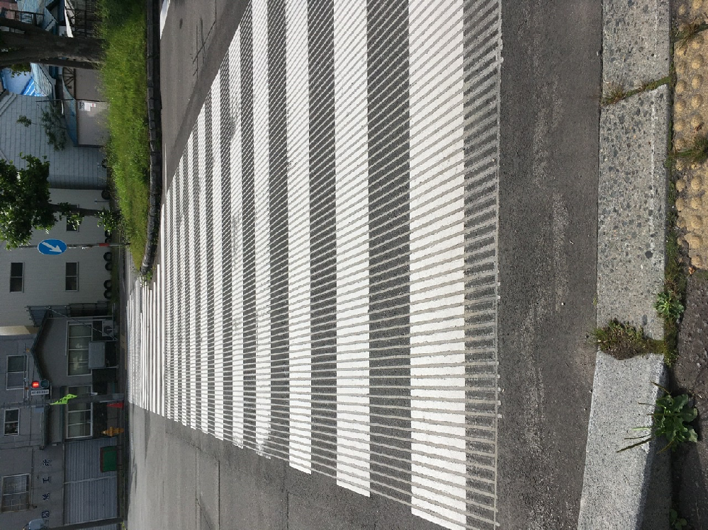 音が出る横断歩道 先日、出先で見慣れない横断歩道を見かけました。写真のように細かく溝が掘られていて、車が通ると「ズー」みたいな鈍い音がしていました。しばらく観察して考えてみたものの、この音が出る仕組みが何の為にあるのか分からずとても気になっています。 この横断歩道はなぜ音を出すのですか?どういった役割を担っているのでしょうか?全国各地にあるのかそれとも地域性があるのか、などなど何か分かる方がいらっしゃったら教えていただけると嬉しいです。 よろしくお願いします!