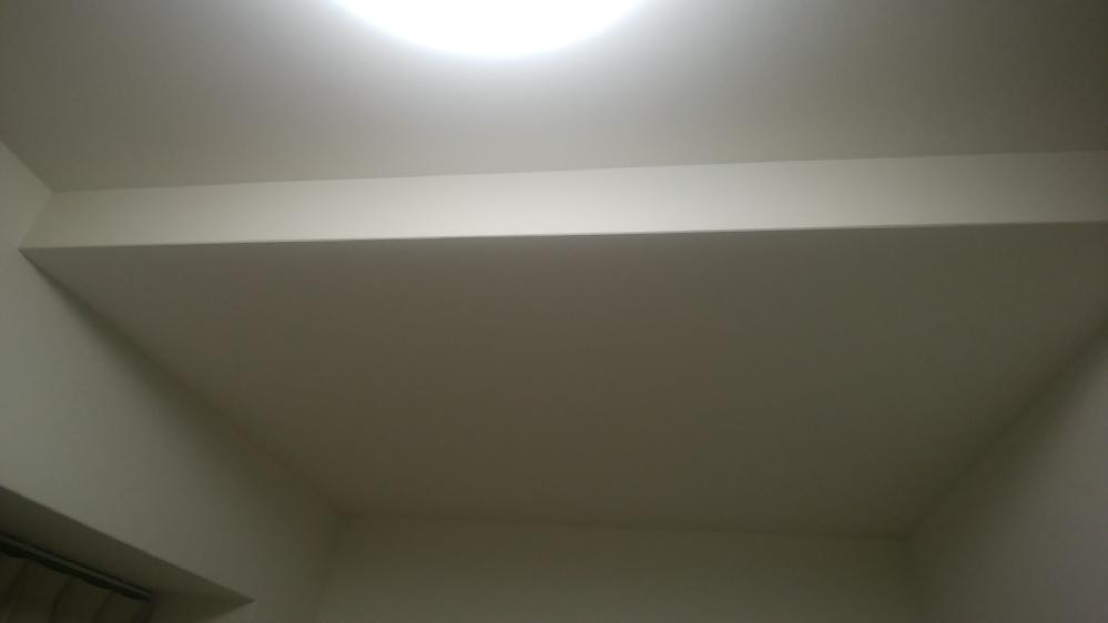 本棚の転倒防止のために天井に突っ張り金具を設置しようと思うのですが、少し変則的な形をしていてどこに下地?が入っているのか分かりません このような形状の天井の場合、どの辺にどの向きで下地が入っていると思われますか? 金具を設置したいのは画像の奥、一段下がった天井の壁寄りの位置です 参考として、ちょうど真ん中当たりを軽く叩いてみたところ音が響くような感じがしました
