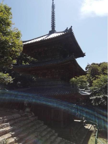 安土城跡地の三重塔の写真を撮ったのですが、下の青白いカーブを描いているものは心霊的なあれでしょうか? ただの光でしょうか