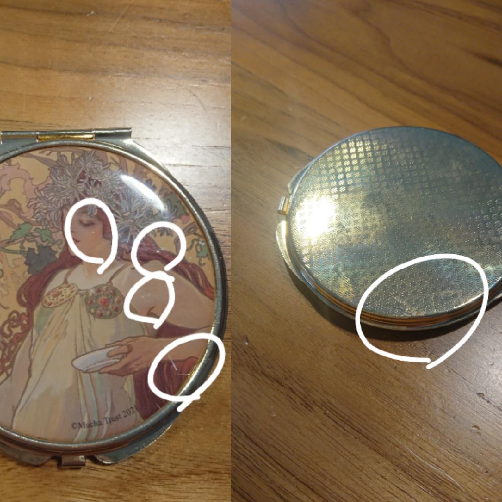 サリュとミュシャがコラボした商品について 私は先日、オンラインでサリュとミュシャがコラボした商品の中のコンパクトミラーを買いました。ですが画像の左側のように傷が計4つ、ついていました。また画像の右側の様に裏側にも何かついていました。これって交換可能なのかどうかわかる方いらっしゃいますか? こんな小さい傷、気にするなと思う方もいらっしゃると思いますが、やっぱり楽しみにしていた分ショックが大きくて、、