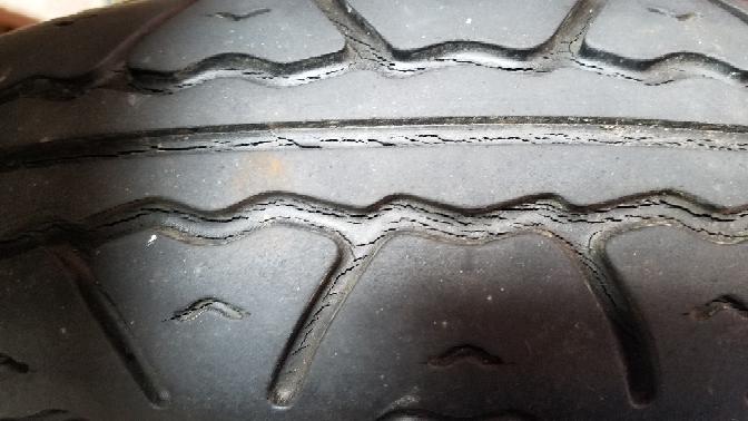 バイクのタイヤですが、先日車検に出しましたが指摘無く合格しました。走行中はしっかりグリップしていますが、先ほど亀裂が気付きました。爪で押した感じではカチカチになっているイメージでは無かったのですが、 まだ使ってもいいのか、交換するべきかご意見お待ちしております。バイクは少ないお小遣いで遣り繰りしており、ダンロップのそこそこ良いタイヤなので後一年使えれば御の字です。。