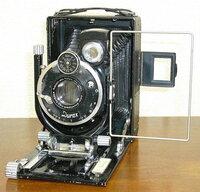 画像は六桜社製の大名刺判(6.5x9cm)リリーです。このカメラに付いているシャッターチャージが不要な国産デュラックス(Dulax)シャッターはどのようなシャッターを手本に造られたと思われるでしょうか? また、このカメラに付いている六桜社製オプター(Optor)レンズは何群何枚設計でしょうか?