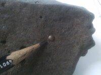 最近河原で変わった石を拾いました。 よく見ると断面に直径5mm位の金属の球状の物が顔を出しています。  一瞬隕石?と思いましたが、webで調べてみると製鉄の際に出るスラグ(からみ)に近いように思いました・・・ 全体的には、一部発泡部分が見られ、磁性もあります。スラグは磁性があるようなので、隕石と間違えて(隕鉄)鑑定の依頼があるそうなのですが、スラグの中に金属の結晶体が残る事ってあるので...
