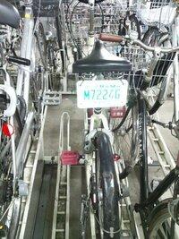 自転車のナンバープレート 近所の大型自転車専門店で、廉価な自転車(店頭に並んでたもの)を購入しました。 が、駅前の駐輪場で、同じ自転車(もしくは似たような自転車)が沢山停まっていて、探すのに苦労してしまいます。  駐輪場で、ナンバープレートのようなものをサドルの下につけている自転車を見かけました。 写真を添付しました これは、一目で自分の自転車が判別できて、良いな、と思いましたが、...