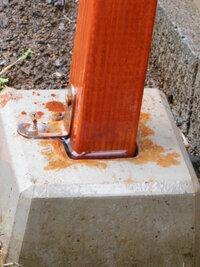 フェンスの支柱に雨水が溜まってしまいます。 DIYでウッドフェンスを作ったのですが、写真のように支柱を支えている石?に雨水が溜まってしまいます。数時間すれば無くなっているのですが、雨水はたまらないように塞いだ方が良いですか?  よろしくお願いします。